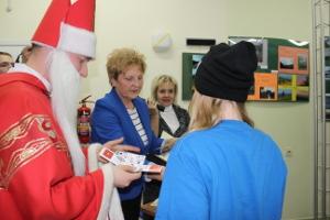 Św. Mikołaj w towarzystwie Dyrektora OPS - Elżbiety Krzak i Dyrektora OK - Małgorzaty Wójcik wręcza podziękowania wolontariuszce
