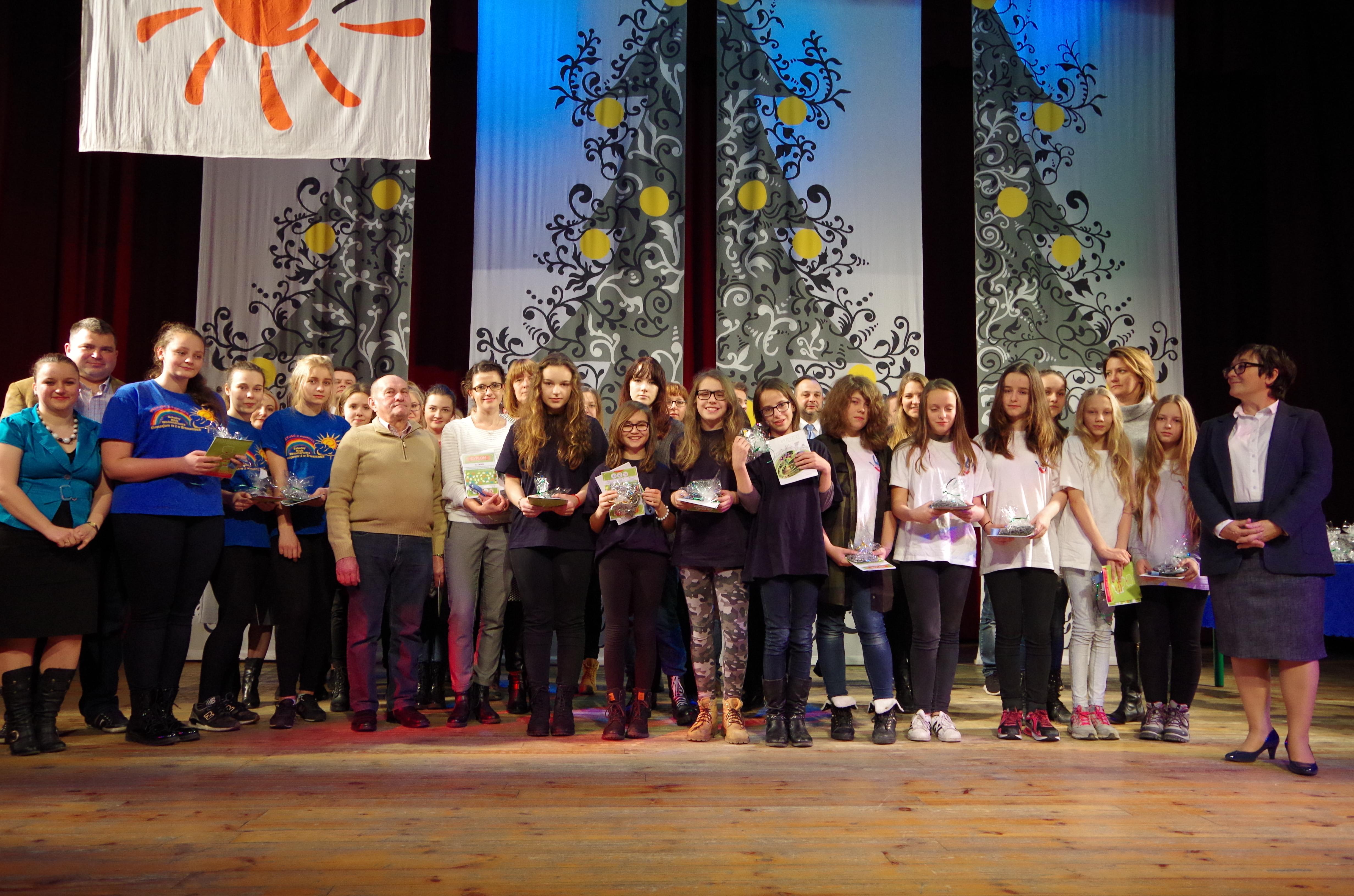 Grupa wolontariuszy i zaproszonych gości stojąca na scenie Ośrodka Kultury w Brzeszczach. Wolontariusze trzymają w rekach podziękowania - dyplomy i białe serca plecione z papierowej wikliny