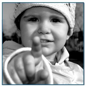 Mała dziewczynka wyciąga przed siebie dłoń i wskazującym palcem pokazuje przed siebie - kliknij aby powiększyć grafikę