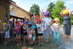 grupa dzieci i dorosłych z kolorowych perukach i okularach skacząca w górę